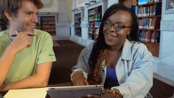 Um tutor de línguas ensinando um aluno de línguas em uma biblioteca