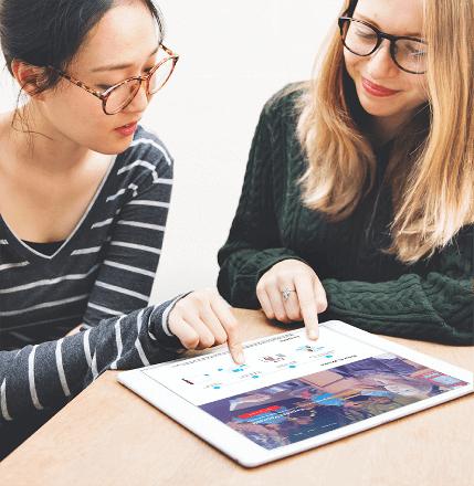 Taalleraar en taalstudent in een persoonlijke les kijkend naar een tablet
