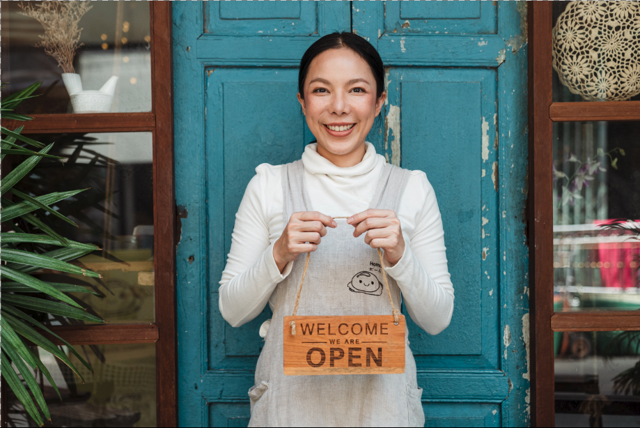 A small business owner holding the sign for her business