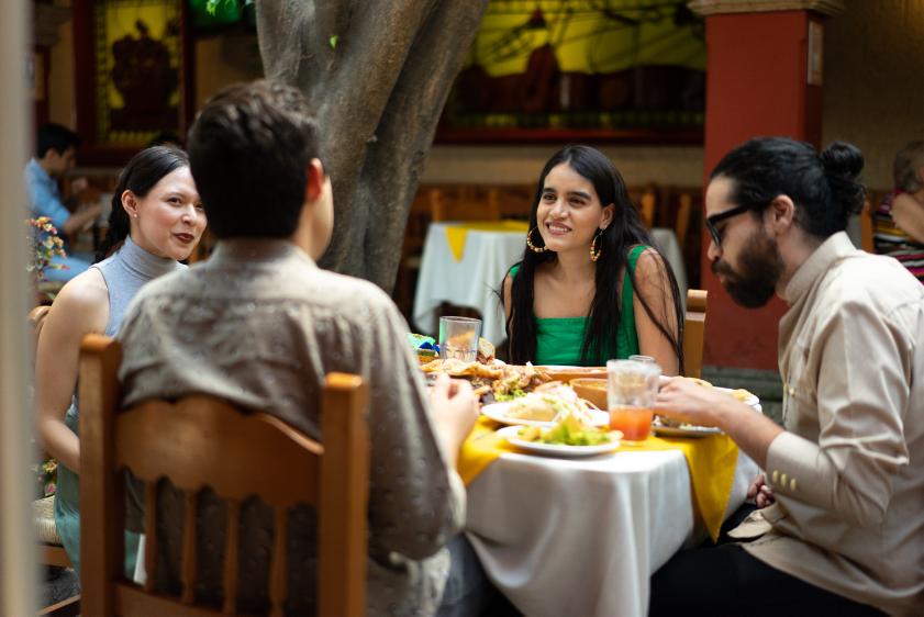 Quatro amigos desfrutando de uma refeição juntos em um restaurante