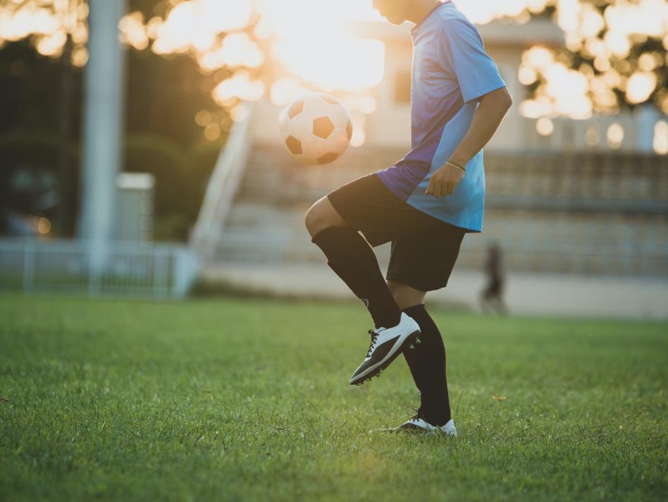 Jogador de futebol treinando sozinho em um campo