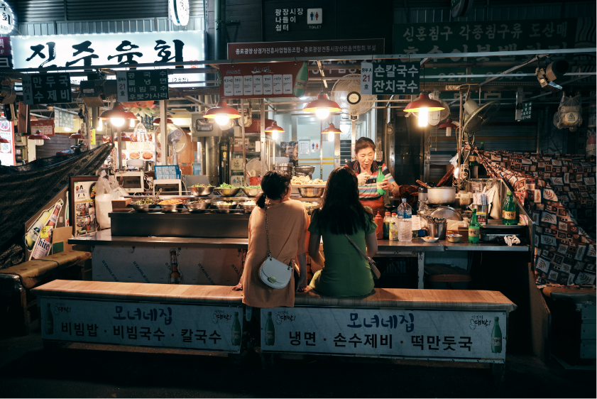 Two friends enjoy a meal together at a restaurant in Seoul, South Korea