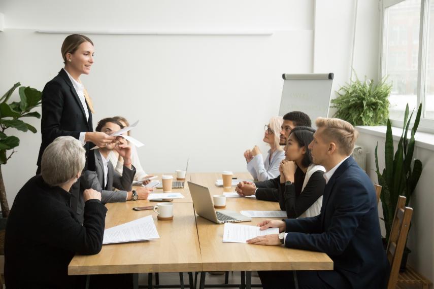 امرأة تقدم عرضًا تقديميًا في اجتماع عمل